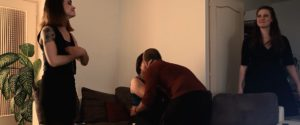 Un couple s'embrasse sur un canapé, deux femmes sont présentes et ont l'air ravies