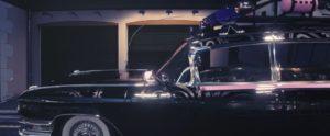 Voiture SoftBusters noire et rose, devant garage, porte fermée