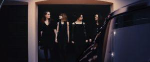 Voiture SoftBusters noire et rose, devant garage, quatre jeunes femmes se tiennent devant la porte du garage et se regardent