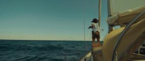 Femme sur bateau regardant l'ile avec des jumelles
