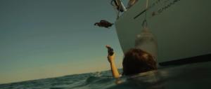 Femme dans l'océan visant drone avec pistolet fusées de détresse