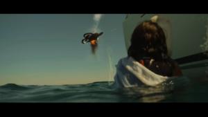 Femme dans l'eau qui tire sur un drone avec une fusée de détresse.