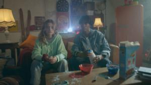 Deux jeunes assis sur un canapé vont prendre leur goûter, des céréales et du lait. Derrière eux, une boule disco réalisé en VFX par Tronatic Studio, Paris et Tours