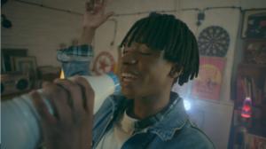 Jeune homme entrain de chanter avec une bouteille de lait en guise de micro, derrière lui une boule disco réalisé en VFX par Tronatic Studio, Paris et Tours