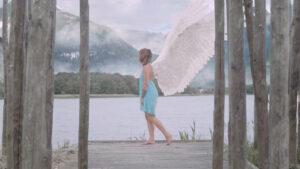 Femme avec des ailes, bord de l'eau, montagnes