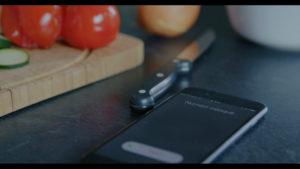Téléphone qui sonne, sur un plan de travail, tomate, oignon, couteau, planche à découper